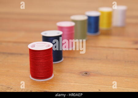 Row of multi-colored cotton reels or bobbins on a wooden sewing table - Stock Photo