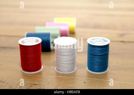 Multi-colored cotton reels or bobbins on a wooden needlework table - Stock Photo