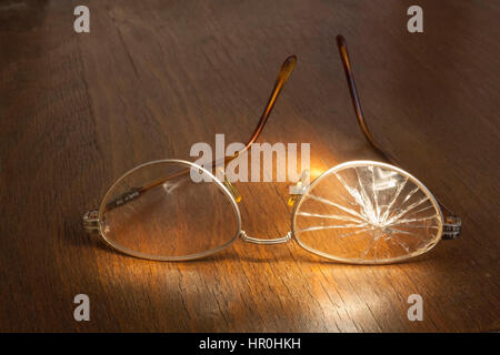 photo of broken glasses on wooden background - Stock Photo