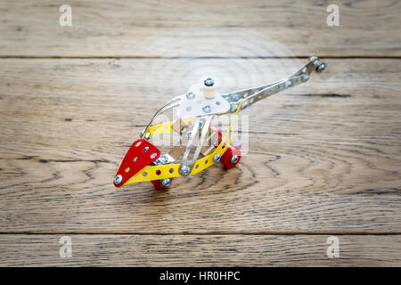 Children helicopter of metal designer with spinning propeller on the wooden table - Stock Photo
