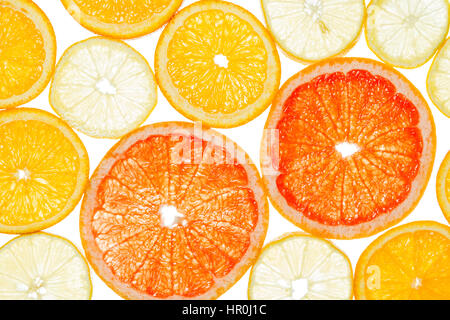 Lemon, grapefruit and orange cut by segments located close photographed against the light isolated on white background - Stock Photo