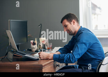 Successful young businessman going through paperwork while sitting at his desk and computer in his modern office - Stock Photo