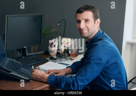 Portrait of a smiling young businessman going through paperwork while sitting at his desk and computer in his modern - Stock Photo