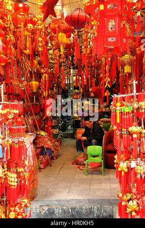 HANOI, VIETNAM - FEBRUARY 19, 2013: A seller man waiting for clients in his small shop full with souvenirs for tourists - Stock Photo