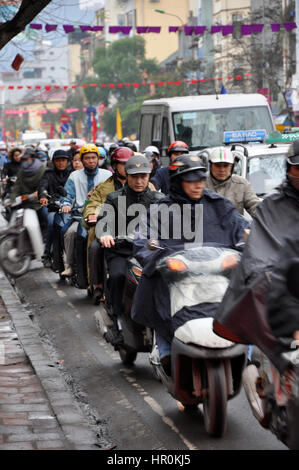HANOI, VIETNAM - FEBRUARY 19, 2013: Crowd of people with scooters blocked in a traffic jam, waiting for green light - Stock Photo