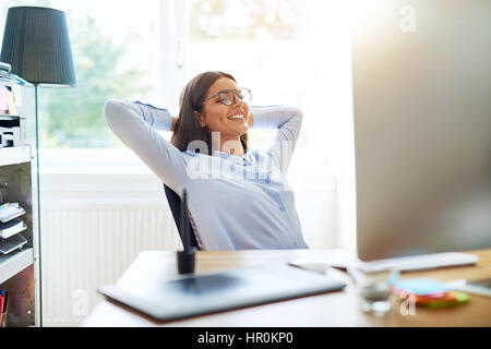 Happy single woman in long sleeve shirt and eyeglasses with arms folded behind head while seated at desk - Stock Photo