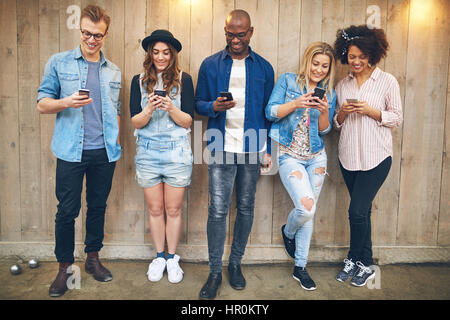 Group of young people at party or meeting wearing casual clothes standing near wooden wall all staring at their - Stock Photo