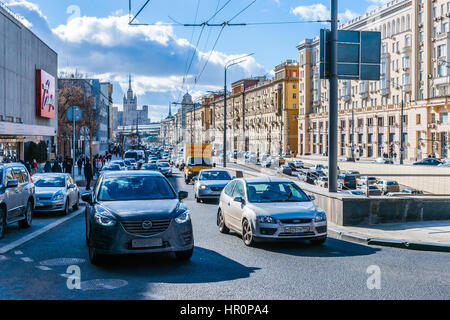 Moscow, Russia. Saturday, Feb. 25, 2017. Busy traffic past the Moscow Academic Theatre of Satire (left). Sunny day - Stock Photo