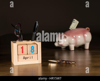 Wooden letters in calendar showing tax day for filing is April 18 2017 with savings piggy bank in background - Stock Photo