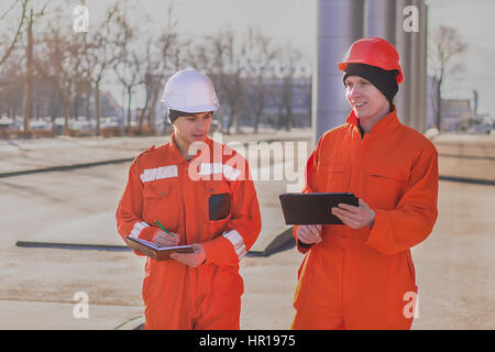 Cheerful young builders in orange uniform with the tablet and notepad. Horizontal outdoors shot. - Stock Photo