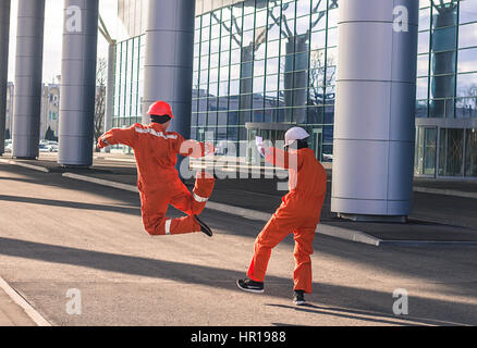 Back view of happy builders in red uniform walking away. Horizontal outdoors shot. - Stock Photo