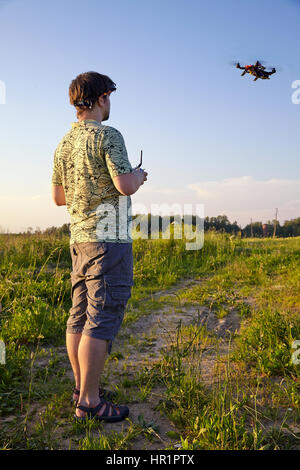 Father and son controls RC drone quadrocopter in the sky - Stock Photo
