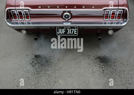 1967 classic burgundy Ford Mustang Coupe with water in the exhaust fumes as the V8 engine warms up - Stock Photo