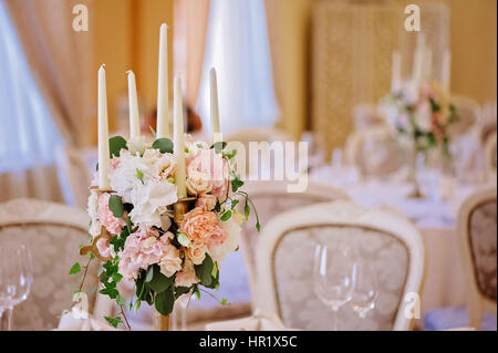 Guest tables with candlestick in rich decorated wedding banquet room - Stock Photo