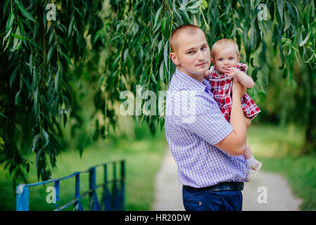 father and daughter. man and beautiful little girl outdoors in park in summer - Stock Photo