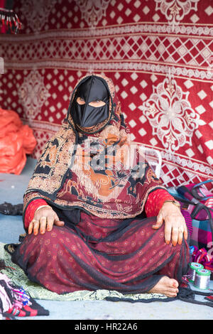 Muscat, Oman - Feb 4, 2017: An old Omani woman dressed in a traditional clothing showing off her wares on a market. - Stock Photo