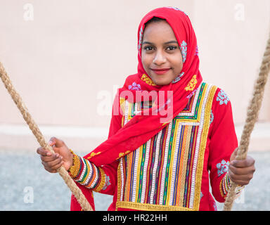 Young Omani girl in a red traditional dress sitting on a swing. - Stock Photo