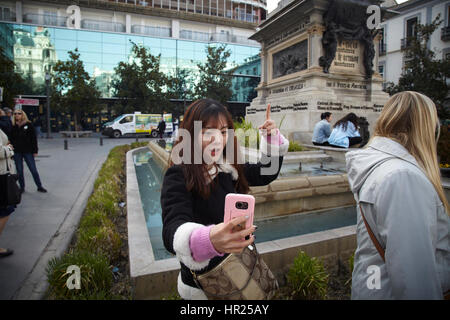 A girl take a selfie in front of Queen Isabelle and Cristopher Columbus In Granada. Spain - Stock Photo