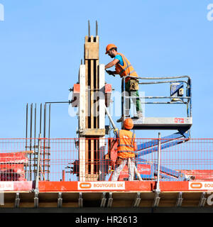 Health and safety  building construction site workers fixing column formwork working together hard hats & high visibility - Stock Photo