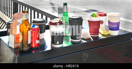 Rubbish left from lunch break office workers after snacking in street beer bottle paper cups coffee cup cans garbage - Stock Photo