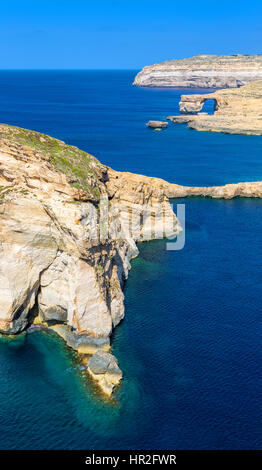 Gozo, Malta - The Fungus Rock and the Azure Window at Dwejra bay on a beautiful summer day with clear blue sky sea - Stock Photo