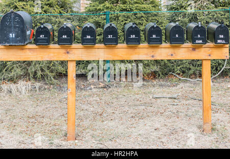 a bank of black mail boxes with numbers - Stock Photo