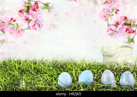 Easter eggs in grass with beautiful Crab Apple blossoms hanging overhead. Extreme shallow depth of field with selective - Stock Photo