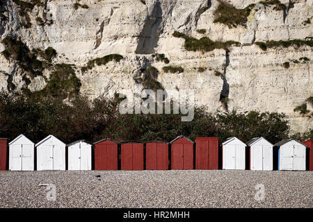 A row of white and red beach huts sit at the bottom of a chalk cliff on a pebble beach - Stock Photo