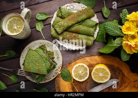 pancakes with spinach on wood table. Top view. Lay flat. - Stock Photo