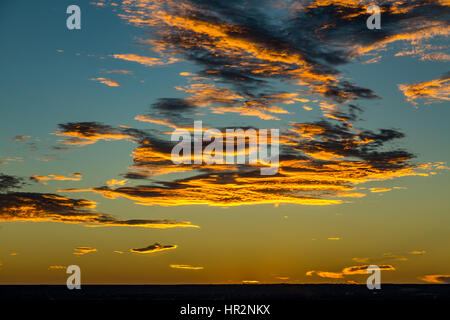 The sun sets over Albuquerque, New Mexico lighting clouds in the sky from underneath. - Stock Photo