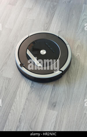 robotic vacuum cleaner on laminate wood floor smart cleaning technology - Stock Photo