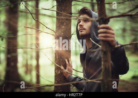 Hooded guy in the woods exploring nature, individuality and freedom concept - Stock Photo