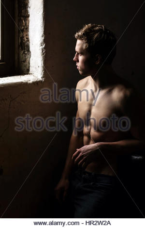 Shirtless young man near a window - Stock Photo