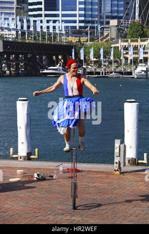 Street Performer balancing on Unicycle  in Harbor of Sydney, Australia - Stock Photo