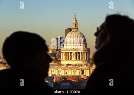 St Paul's Cathedral seen through between two unidentified tourists - Stock Photo