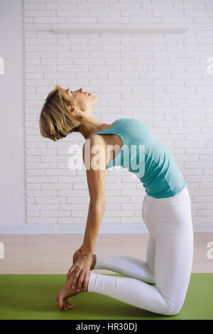An attractive young woman doing a yoga pose for balance and stretching. vertical photo. Healthy concept - Stock Photo