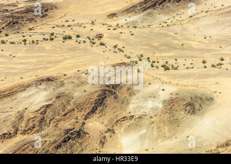 Aerial image from a flight over Kaokoland in Namibia.  The ever changing colours of the desert below with dried - Stock Photo