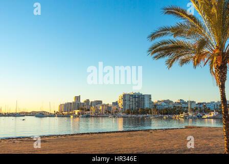 Late afternoon sun falls on beach, marina & boardwalk.  St Antoni de Portmany, Ibiza, Spain.  Empty beach & calm - Stock Photo