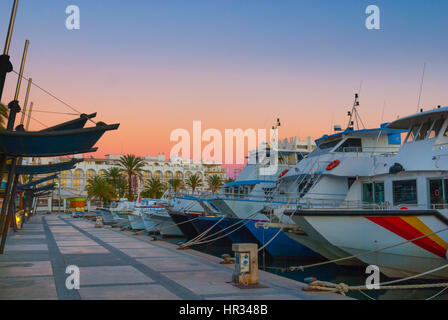 Boats in for the evening in marina harbor under dramatic magenta sunset color .  End of a warm sunny day in Ibiza, - Stock Photo