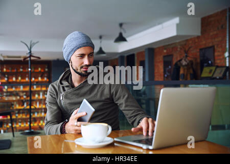 Young handsome hipster man with beard is using computer in cafeteria - Stock Photo