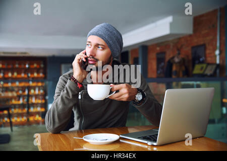 Young handsome hipster man with beard sitting in cafe talking mobile phone, holding cup of coffee. Laptop on wooden - Stock Photo