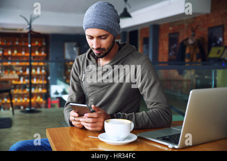 Young handsome hipster guy at the restaurant using a mobile phone. - Stock Photo
