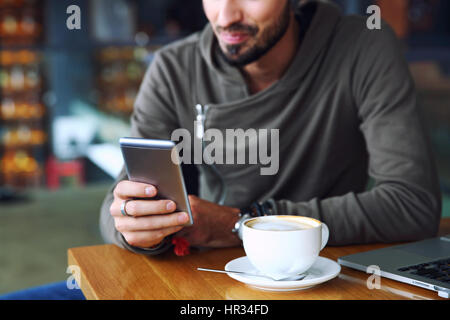 Young handsome cheerful hipster guy at the restaurant using a mobile phone, hands close up. Selective focus. - Stock Photo