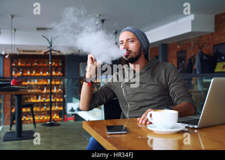 Young handsome hipster man with beard sitting in cafe with a cup of coffee, vaping and releases a cloud of vapor. - Stock Photo