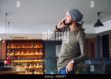 Young handsome hipster man using smartphone in cafe - Stock Photo