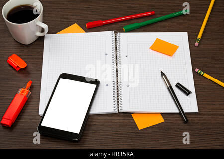 Opened notebook, smartphone with blank screen, pen, sticky note, cup of coffee in chaos on dark office wooden desk. - Stock Photo