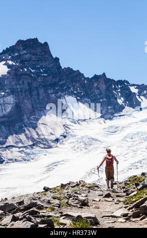 A woman hiking on the Burroughs Mountain trail in Mount Rainier National Park, Washington, USA. - Stock Photo