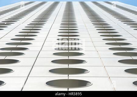 Upwards perspective of the distinctive circular windows of Jardine House, Hong Kong - Stock Photo