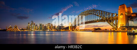 Sydney. Panoramic image of Sydney, Australia with Harbour Bridge during twilight blue hour. - Stock Photo