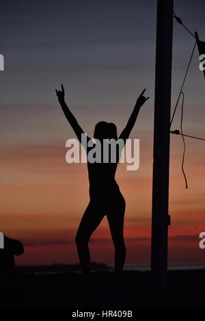 Silhouettes of female volleyball players practicing volleyball on a beach at sunset in Mission Beach, San Diego, - Stock Photo